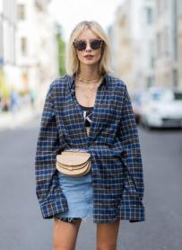 BERLIN, GERMANY - JULY 17: Lisa Hahnbueck wearing a checked Balenciaga men button shirt, a beige Chloe belt bag, a denim mini skirt, Dior ankle boots, sunglasses, a black Calvin Klein cropped top on July 17, 2017 in Berlin, Germany. (Photo by Christian Vierig/Getty Images)